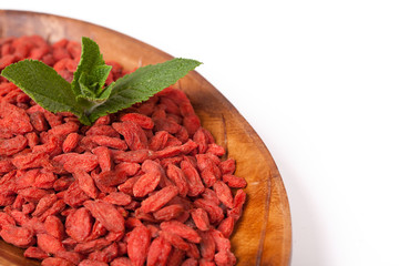 red dried goji berries in a wooden bowl isolated on white
