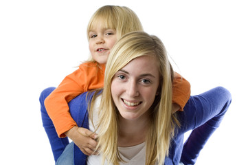Teenage girl piggybacks a todler.