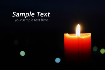 A single burning orange candle isolated