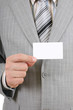Young businessman showing a blank business card