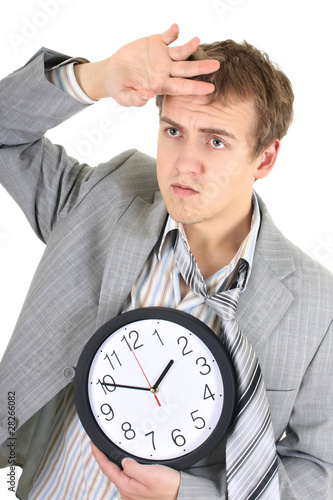 Tired businessman in grey suit holding a clock