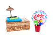 a wicker suitcase with beach ball and toys isolated over white