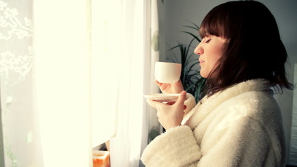 Young smiling woman haivng a cup of tea