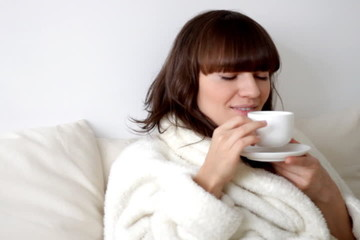 Young smiling woman haivng a cup of tea in bed