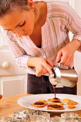 Frau überzieht die Plätzchen mit Schokolade