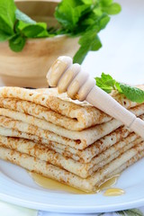 Traditional Russian pancakes with honey on a plate