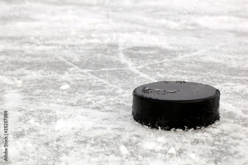 Leinwandbild Motiv black hockey puck on ice rink