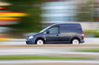 Speedy  dark minivan  is  going on road, panning and blur