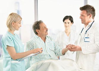 Doctors talking to old patient in hospital