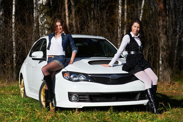 Two beautiful girls and stylish white sports car