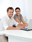 Portrait of a couple with a laptop at a table in the living room