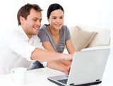 Cute man showing something on the laptop screen to his wife