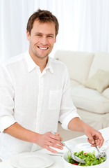 Joyful man serving salad standing at a table in the living room