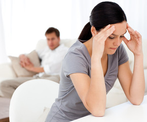 Man looking at his girlfriend having a headache sitting at a tab