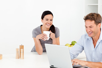 Cheerful couple looking at something on internet while drinking