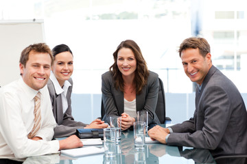 Portrait of a businesswoman with her team sitting at a table