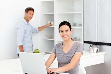 Happy woman on the laptop while her husband preparing coffee
