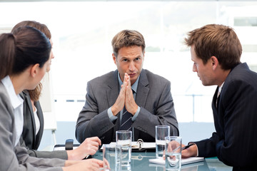 Serious manager talking to his team during a meeting