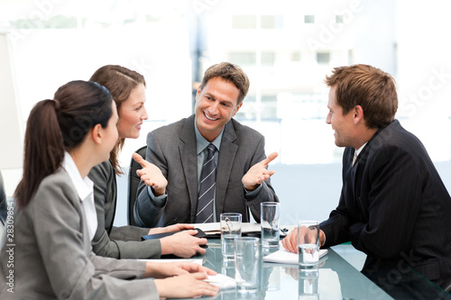 Delighted managertalking to his team at a table