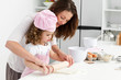 Mother and daughter using a rolling pin together