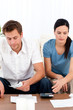 Desperate couple looking at their bills sitting on the sofa