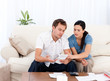 Man showing a bill to his girlfriend sitting on the sofa