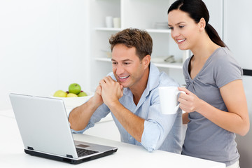 Happy couple looking at something on the laptop