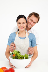 Happy man mixing a salad with his girlfriend in the kitchen