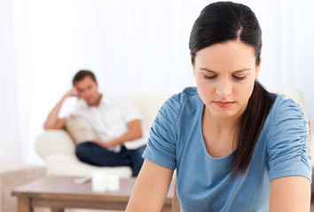 Woman thinking at a table while her boyfriend waiting