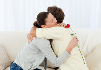 Lovely woman hugging his boyfriend after receiving a flower