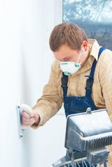 Young man builder polishing the wall. house environment theme
