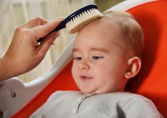 Mother combing her baby's hair