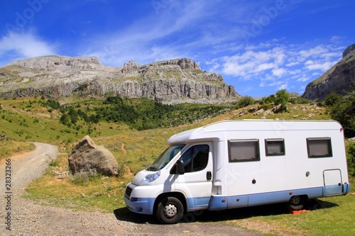 Camper van in mountains blue sky