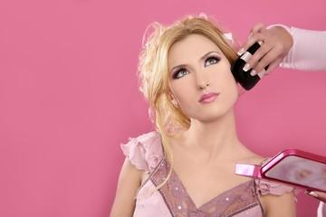 Makeup artist hand working on beautiful blonde face
