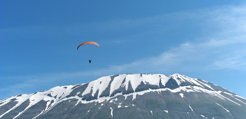 A paraglider soars over a snow-capped mountain