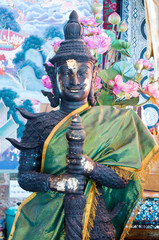 buddhist deva statue with green cloth in church