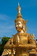 Golden buddhist deva statue with blue sky at temple