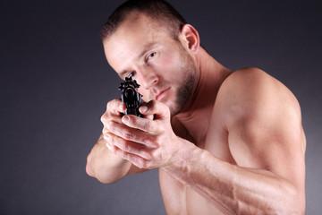 Mann mit Pistole zielt, quer