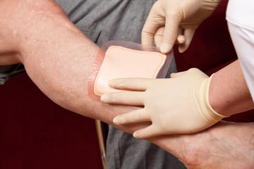 Wundversorgung mit Pflaster durch Krankenpfleger