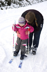 Mother teaching small child cross country skiing