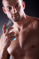 Sportlicher Mann sprüht Parfüm