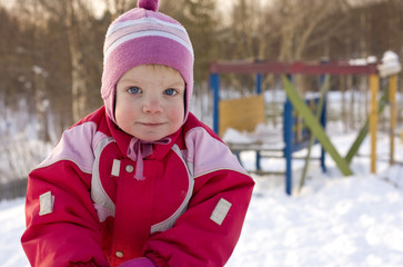 Cold little girl on a kindergarten playground in wintertime