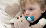 Tired child with pacifier and teddy bear