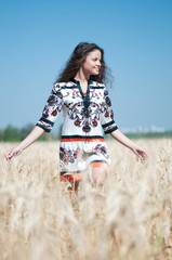 Beautiful woman walk in wheat field on sunny summer day.