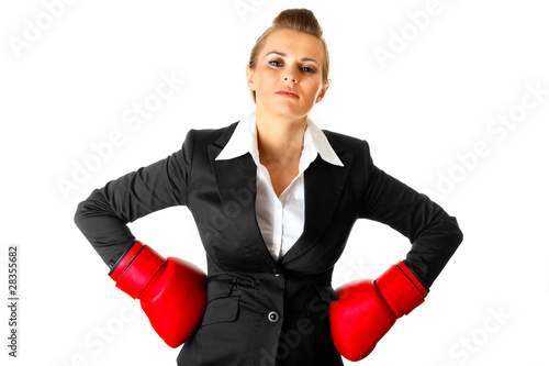 Business woman holding hands with boxing gloves on hips