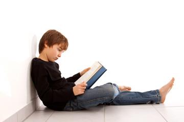 Junge liest am Boden sitzend, konzentriert ein Buch