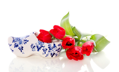 A Dutch ceramic Delft Blue clog with red tulips isolated over wh
