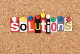 The word Solutions in magazine letters on a notice board poster