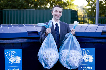 A businessman recycling bags of shredded paper