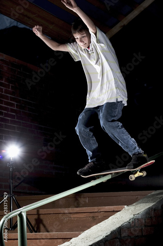 skateboarder doing a trick on the rail
